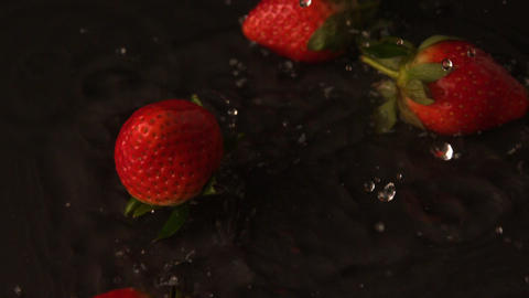 Strawberries falling on wet black surface Footage