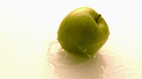 Apple falling and spinning on wet white surface Footage