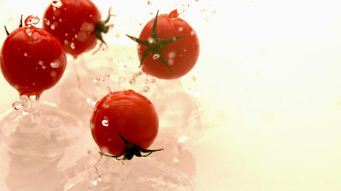 Cherry tomatoes falling on white wet surface Footage