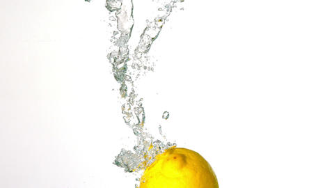 Lemon plunging into water on white background Footage