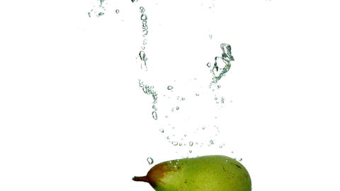 Pear plunging into water on white background Footage