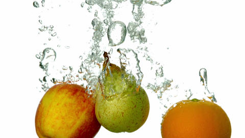Pear apple and orange plunging into water on white Footage