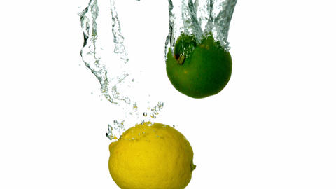 Lime and lemon plunging into water on white backgr Footage