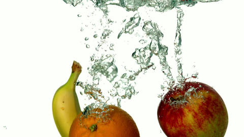 Banana apple and orange plunging into water on whi Footage
