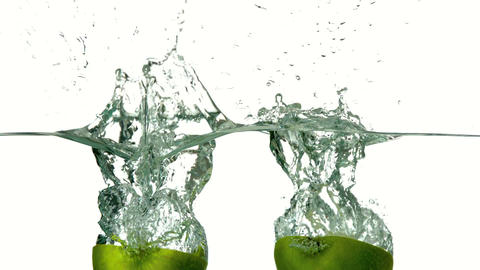 Apple halves plunging into water on white backgrou Footage