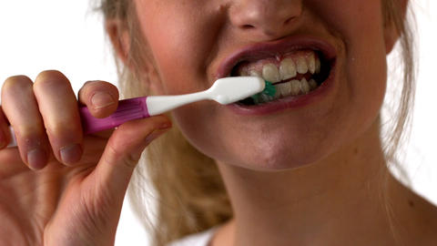 Woman brushing her teeth on white background Footage