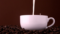 Milk pouring into white coffee cup Footage
