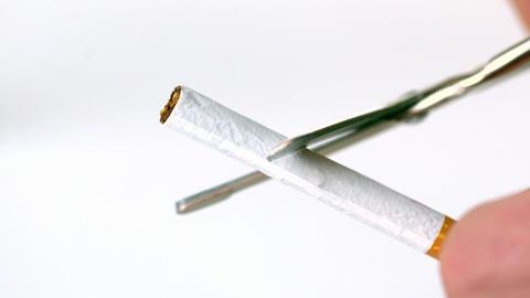 Scissors cutting a cigarette in half Footage
