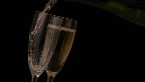 Champagne pouring into flutes on black background Footage