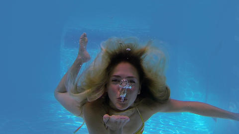 Pretty blonde swimming towards camera and blowing kiss Footage