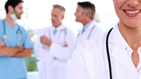 Doctor smiling at camera with team behind her Footage