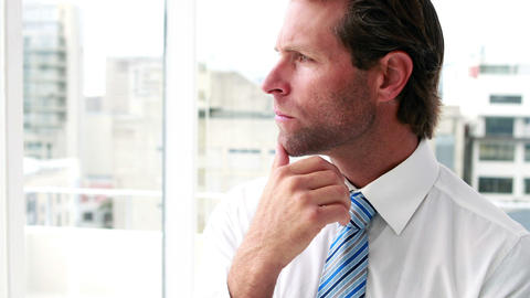 Handsome businessman thinking and looking out window Footage