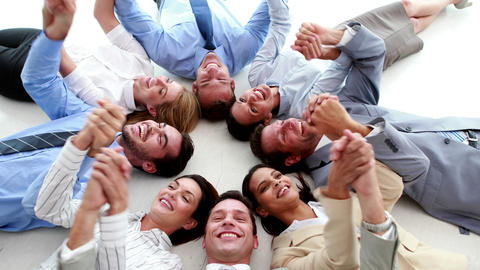 Business people lying in a circle holding hands Footage