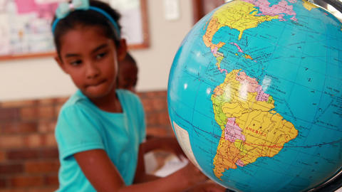 Little girl looking at globe and writing in classroom Footage