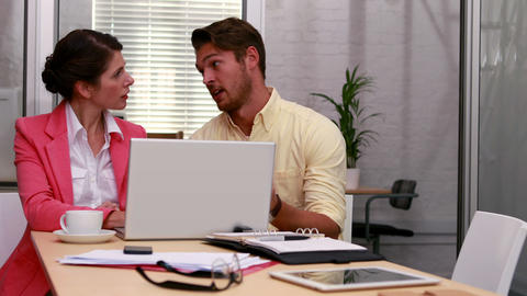 Casual business partners working together on laptop Footage