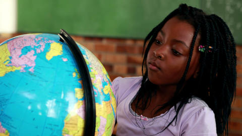 Cute pupils looking at the globe in classroom Footage