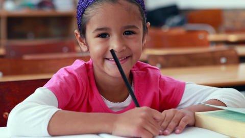 Cute little girl colouring in book in classroom smiling at camera Live Action