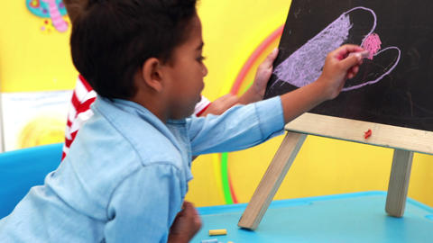 Cute little boys drawing on mini chalkboard Footage