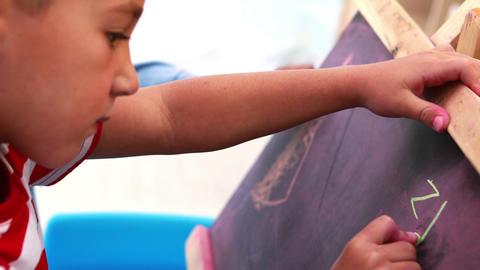 Cute little boys drawing on mini chalkboard Footage