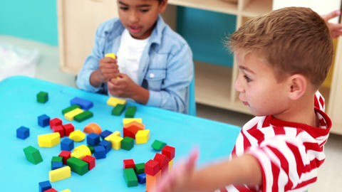 Cute little boys playing with building blocks at table Footage