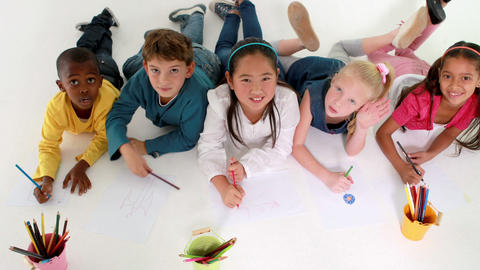 Cute children lying on floor drawing on paper and waving at camera Footage