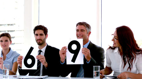 Business people on interview panel showing scores Footage