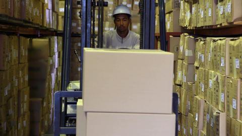 Forklift driver picking up palette of boxes Live Action