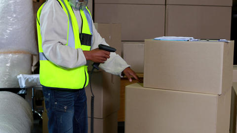 Warehouse worker scanning barcodes on boxes Footage
