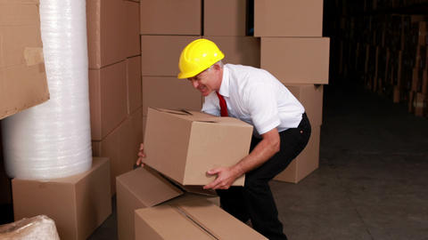 Warehouse manager injuring his back moving boxes Footage