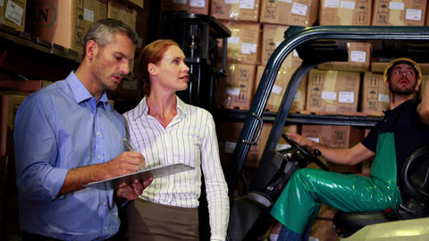 Warehouse management talking with forklift driver behind Live Action