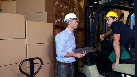 Warehouse manager working with foreman in forklift Live Action