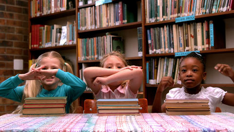 Cute little girls posing with library books Footage