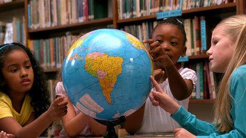 Cute little girls looking at globe in library Footage