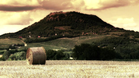 Hay Bale On Harvested Grain Field And Volcanic Hil stock footage