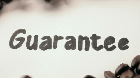 guarantee. written on white under coffee Stock Video Footage