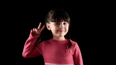 girl shows the Peace on black background Stock Video Footage