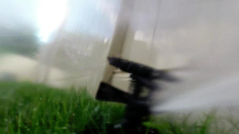Oscillating Lawn Sprinkler Watering Grass In Backy stock footage