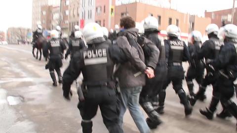 Large group of riot police officers arrest man - H Footage