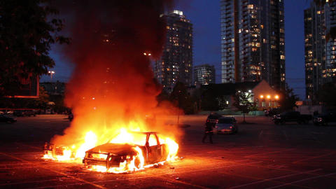 Two Cars Burn In Parking Lot With Highrise At Dusk stock footage