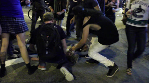 Unconscious man attended by crowd of rioters Footage