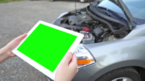 A woman holds a blank tablet PC with a green scree, Live Action