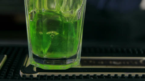 Bartender pouring a glass of ice with mint syrup Footage