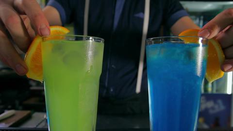 Bartender adorns two cocktails of orange slices. D Footage