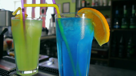 Blue and green cocktails decorated with orange sli Footage