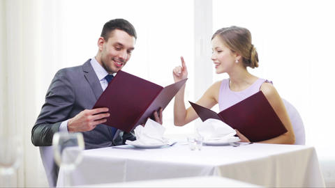 smiling couple with menus at restaurant Footage