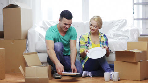 smiling couple unpacking boxes with kitchenware Footage