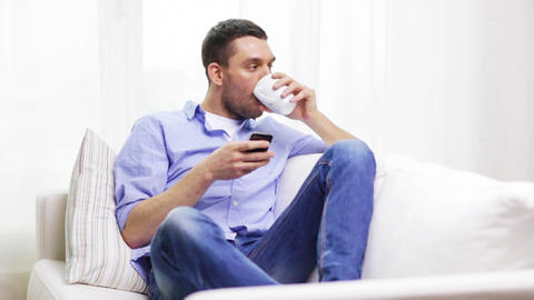 smiling man with smartphone and a cup at home Footage