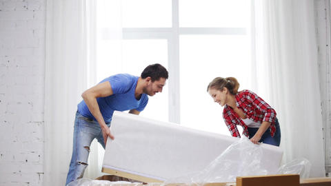 smiling couple opening big cardboard box with sofa Footage