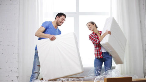 smiling couple opening big cardboard box with sofa Live Action