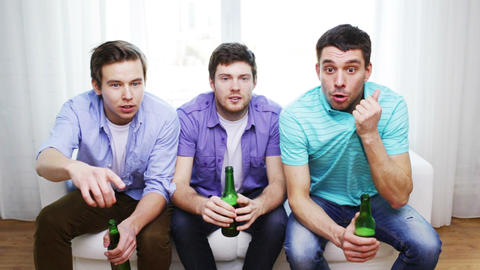 Happy Male Friends With Beer Watching Tv At Home stock footage